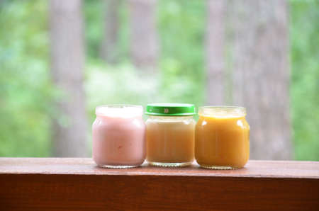 Three jars of baby food nutrition puree mash on the background of foliage. Pink light yellow orange color