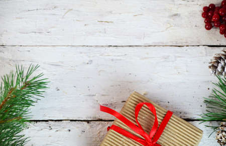 Christmas or new year gift box with decoration. box tied with a red ribbon, a branch of a Christmas tree with cones, top view, flat lay, on a white wooden background