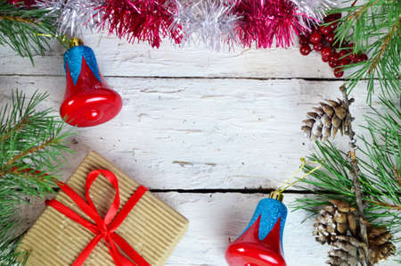 Christmas or new year composition. Christmas gift, two Christmas decorations red blue bell, pine cones, fir branches on wooden white background. Flat lay, top view, copy space Archivio Fotografico