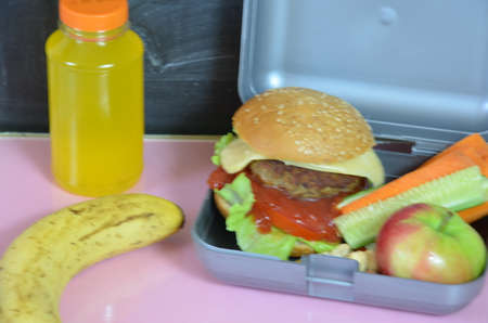 Homemade Hamburgers with lettuce in lunchbox on the table. with bright yellow orange juice. with banana nuts. Sliced vegetables carrots and cucumber. Opposite the school board. Snack. School lunch Zdjęcie Seryjne