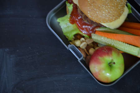 Homemade Hamburgers with lettuce in lunchbox. with orange juice. banana nuts. vegetables carrots and cucumber. On the school black board. Snack. School lunch. back to school. top view copy space Zdjęcie Seryjne