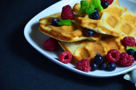 Homemade Belgium Waffles with fresh blueberries for breakfast. White plate, Viennese waffles with raspberries and mint. quick delicious breakfast on black background. top view copy space