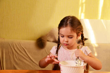 Cute little girl is playing and laughing while kneading the dough in the kitchen Zdjęcie Seryjne
