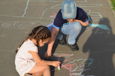 Child drawing sun and house on asphalt in a park on the playground or sidewalk, happy childhood, summer vacation, entertainment for children