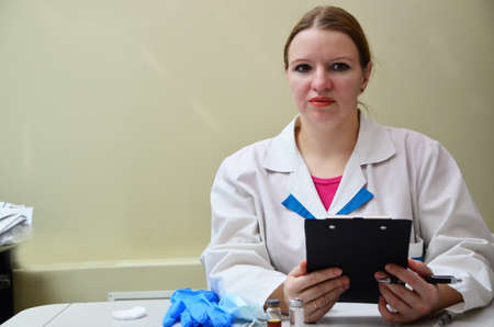 Healthcare. A patient in a doctors office. The doctor enters recommendations and prescriptions