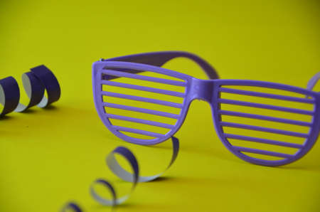 glasses with purple stripes on a yellow background with a serpentine. attributes of a party, birthday, celebration.