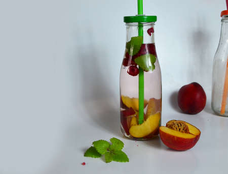 Healthy detox fruit infused flavored water. Summer refreshing homemade cocktail with fruits and thyme on white in a bottle on a white background.