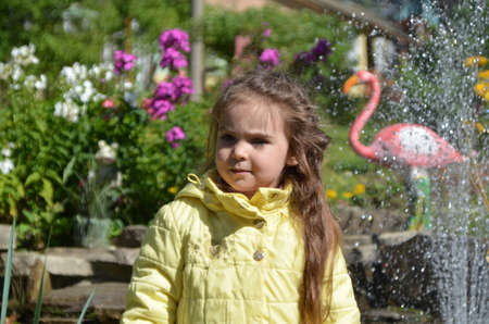 little cute girl walks in the park near the fountain. happy childhood, family. Walking autumn, spring, summer. young girl looking at fountain in city park. girl with long hair in park. Child in happy mood. Standard-Bild