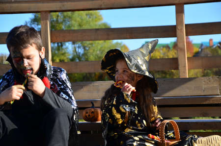children in halloween costumes on holiday a girl in a witch suit a black hat on the head with black Halloween make-up, boy in devil halloween costume with horns zombie eating sweets jelly worms