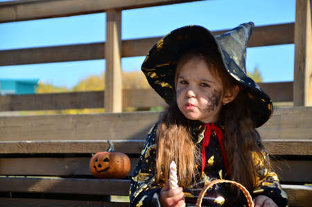 a girl in a witch suit and a black hat on the head with black Halloween make-up, zombie eating sweets jelly worms at a celebration of Halloween Standard-Bild