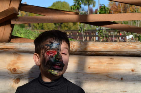 boy with black makeup for halloween, zombie. Scary little boy smiling wearing skull makeup for halloween Standard-Bild