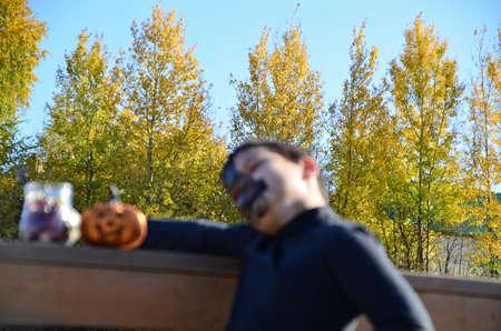 boy with black makeup for halloween, zombie. Scary little boy smiling wearing skull makeup for halloween halloween pumpkin lantern, sweets
