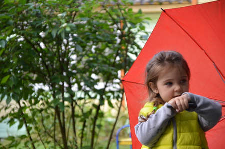 little funny cute girl walks in the rain with a red umbrella, in green rubber boots through the puddles. Laughs, has fun. girl wearing yellow waterproof coat playing on a warm autumn or summer day