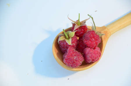 Spoon with ripe aromatic raspberries on table, top view