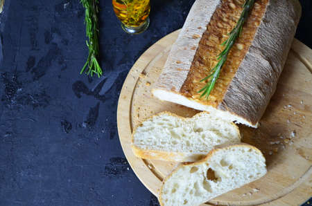 Italian ciabatta bread cut in slices on wooden chopping board with herbs, garlic and olives over dark grunge backdrop, top view Standard-Bild