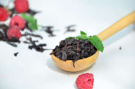 dry black tea in a wooden spoon on a white plate with raspberries and mint. healthy healing berry tea