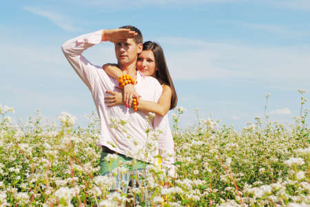 Young couple on field of flowers in sunny day Stock Photo
