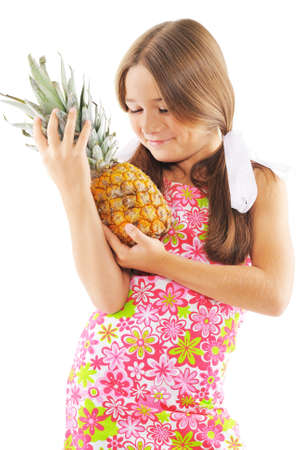 Little girl with pineapple in hands. On white background photo