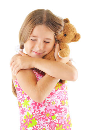Little girl hugging bear toy. On white background photo