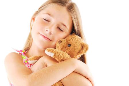 Little girl taking teddy bear on white background