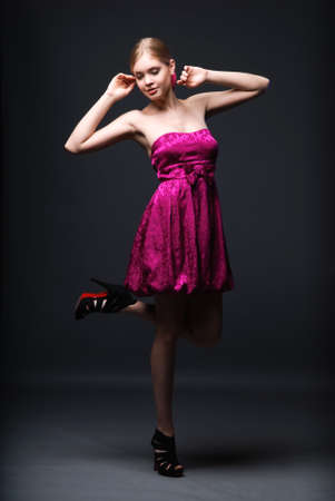 Beautiful young woman wearing pink dress and black high heels shoes