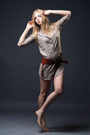 barefooted: Expressive fashion portrait of young woman on dark background barefooted