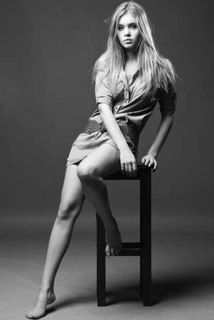 Black and white shot of girl sits on chair with naked legs Stock Photo - 7214851