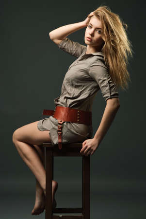 Seductive fashion portrait of young woman sitting on chair Standard-Bild