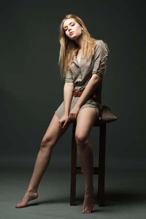 Seductive fashion portrait of young woman sitting on chair Stock Photo