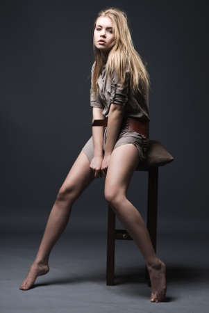 Attractive naked legs blond girl sits on chair Stock Photo - 7214770