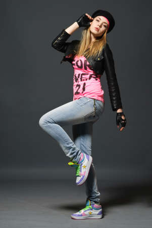 Fashion portrait of young gloved girl wearing on hat, leather jacket, blue jeans and pink t-shirt and bright sneakers