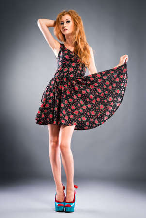 Beautiful red-haired girl on grey background Studio shot photo