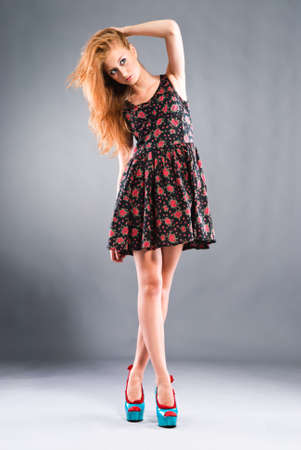 Beautiful red-haired girl on grey background Studio shot Stock Photo