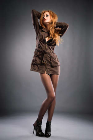 Attractive red-haired girl wearing casual dress and high heels shoes . Studio shot photo