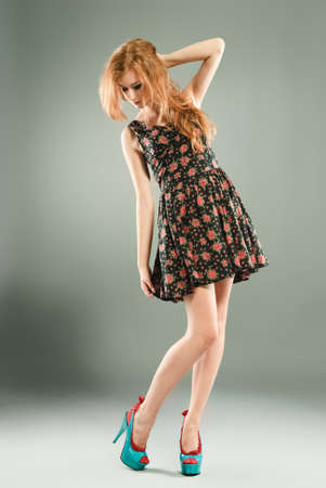 Beautiful red-haired girl on grey background/ Studio shot