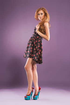 Beautiful red-haired girl on purple background Studio shot photo