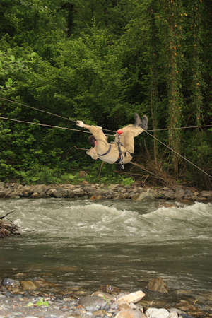 strained: One of methods of ferriage across the river. A tourist crosses the mountain river on the strained rope
