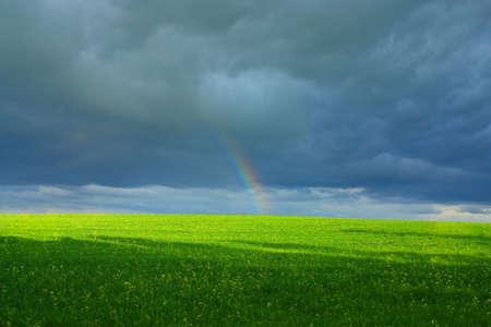 the end of a rainbow: final de arco iris encima del campo verde sobre un fondo de una nube oscura  Foto de archivo