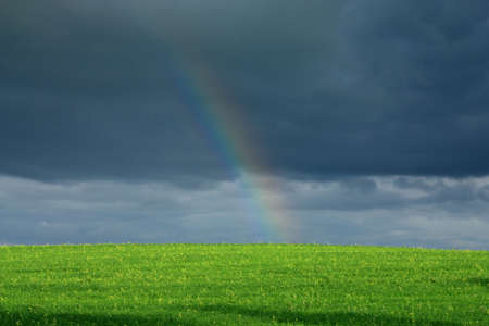 end of rainbow: The rainbow end over a green field against the big cloud