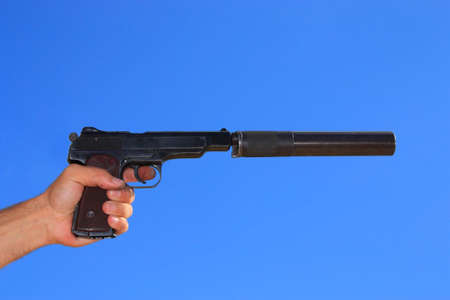 noiseless: Pistol in a hand on a background blue sky. Automatic pistol of Stechkin was produced in a Soviet union. It one of the best autopistols.