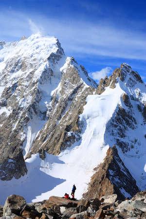 Dos escaladores contra el telón de fondo de las montañas Dij-tau Foto de archivo