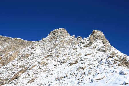 Snow-capped peak and mountainside Ukyu on the background of the blue sky. Caucasus photo