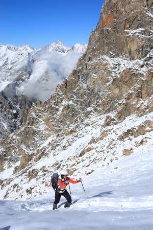 雪が多い斜面に上がって行く女性登山家