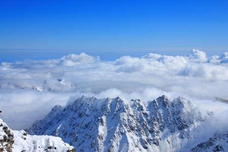 頂上からの眺め。雲および他のピークをはるかに下回る残った 写真素材