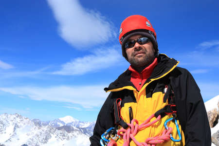 Portrait of a man dressed in climber gear on a soft background of distant peaks photo