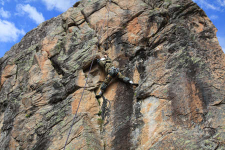rock-climber trains on a difficult granite rock photo