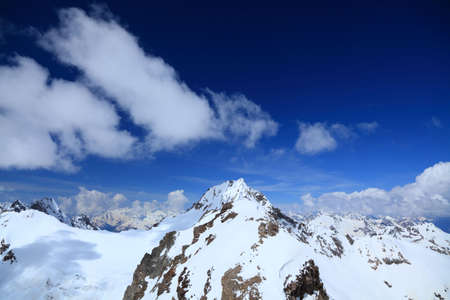 main Caucasus ridge on a background of the blue sky and white clouds Stock Photo - 7256284
