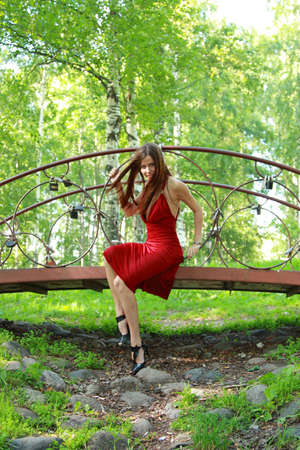 beautiful girl with long hair flowing in the wind, sits on a decorative bridge in the park photo