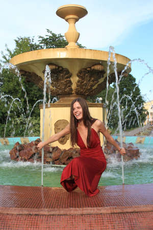 beautiful girl sits at a fountain and touches water streams photo