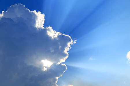 Rays of Sun beaming through clouds in the blue sky photo